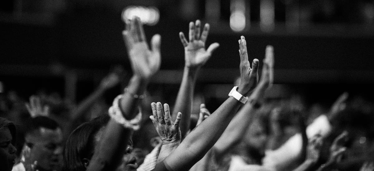 Greyscale photo of raised hands