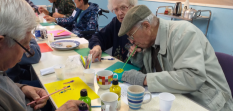 people sitting in a room around a table doing crafts together