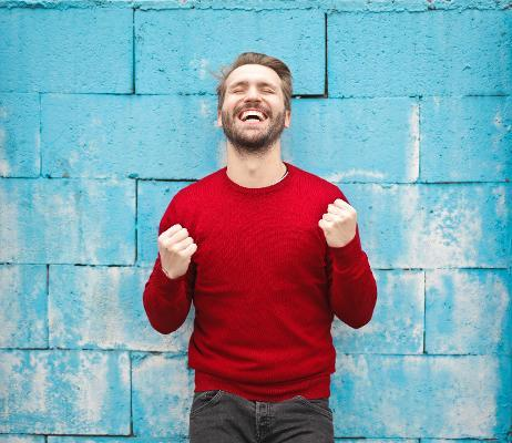 Man in red jumper against a blue wall