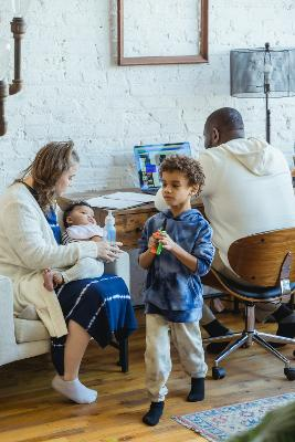 Photo of family in living room man on computer woman feeding baby and boy walking away