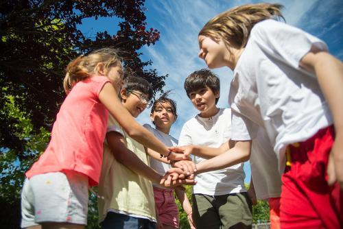 Children with hands together in a group outside