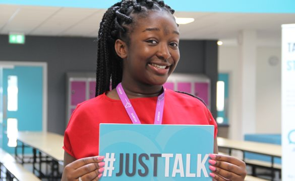 Image of girl holding up Just Talk sign